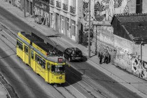 An old yellow tram passes through the streets of Belgrade